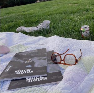 Two copies of second issue of Stuck in Notes magazine by founder and editor-in-chief Kelsey Willock ('15) and creative director Jordyn Albritton ('15), who were roommates at Wake Forest. The magazines are on a quilt on a grass with glasses, tossed aside sneakers and a drink can