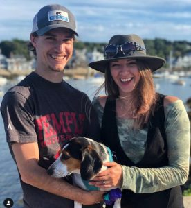 Alex Koblan ('13), her husband, Bart Johnston ('12), and their dog, Luna with the bay behind them.