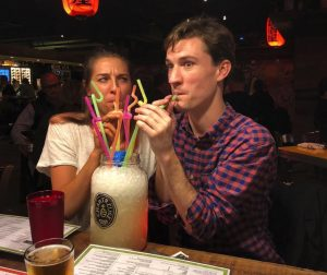Alex Koblan ('13) and her husband, Bart Johnston ('12) sip on a large cocktail in a humorous photo at a bar.