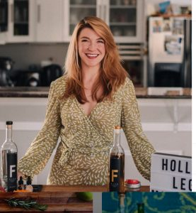 Devin Kidner ('08) stands smiling in front of her countertop at home in front of mixes and ingredients to make cocktails.