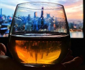 A glass with liquor and a reflection of the Chicago skyline in the background and reflected in the drink by mixologist Devin Kidner ('08)