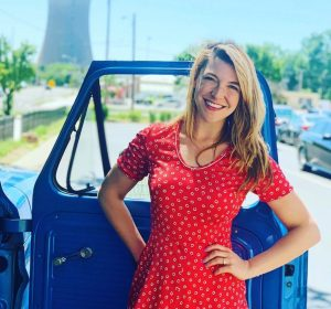Devin Kidner (08) in a red print dress in front of an open passenger side door along a street.