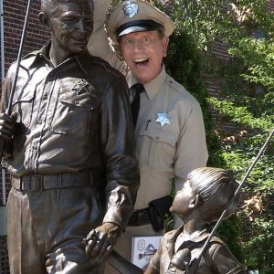 """Actor David Browning mugs for the camera with the bronze statue of Andy and Opie in Mount Airy, says he is """"The Mayberry deputy"""" because no one can replicate Don Knotts' Barney Fife. But his comedic, improvised interactions with fans is classic Barney."""