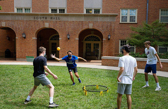 """Students play spikeball outside South Residence Hall, part of """"Freshmanland,"""" a collection of seven dorms for first-year students on South Campus."""