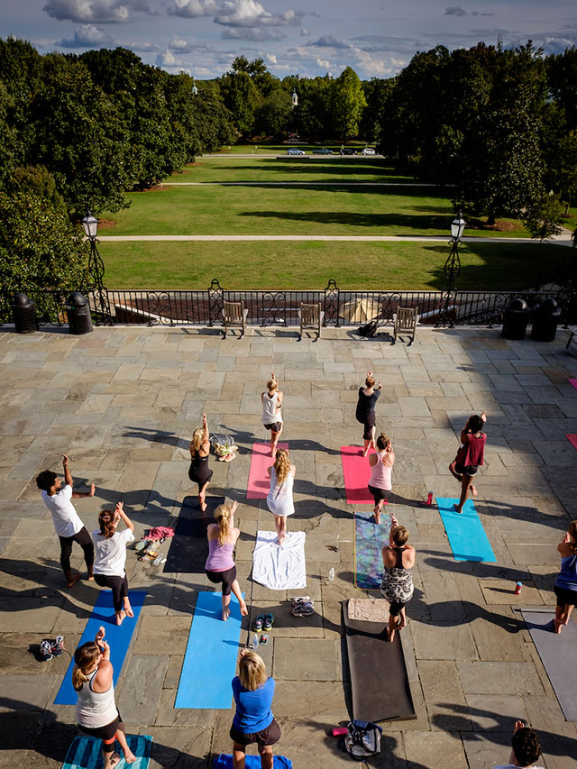 Wake Forest students and staff practice yoga on the Magnolia Patio under the direction of teacher Elliott Watlington on Wednesday, September 30, 2015.