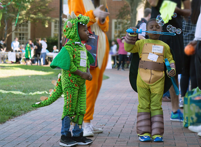 Wake Forest students host local elementary school students on campus for Project Pumpkin, a Halloween celebration.