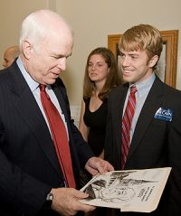 Cartoonist William Warren presents a cartoon he drew of Sen. John McCain when McCain visited campus in May.