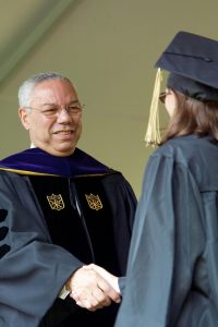 U.S. Secretary of State Colin Powell shakes hands with new graduates.