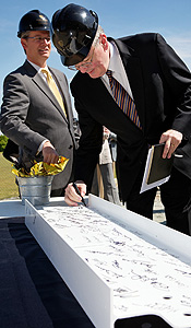 President Nathan Hatch and vice president for university advancement Mark Petersen sign the beam.