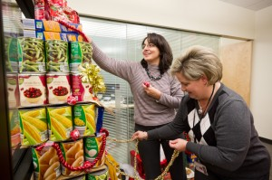 FAS employees Glenda Frye and Angie Downing decorate a food tree.