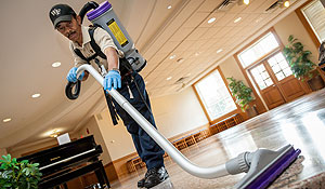 Custodian Charles Nicholson uses a backpack vacuum cleaner.