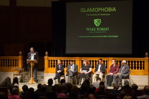 Chaplain Tim Auman introduces panelists Michaelle Browers, Imam Adeel Zeb, Manzoor Cheema, Jade Brooks, Dani Moore, and Khalid Griggs.