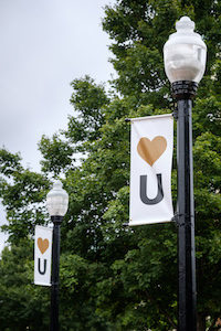 Light pole banners display a heart with the letter U beneath
