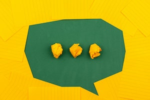 Green chat bubble surrounded by yellow lined papers