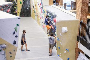 Students wearing masks and using the Wellbeing Center climbing wall
