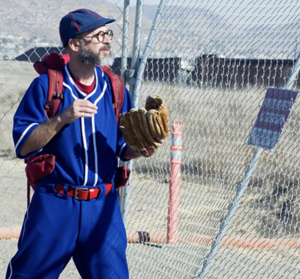 Joel Tauber wearing red, white and blue baseball uniform at US-Mexico border