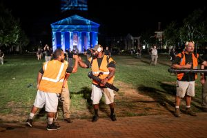 Members of the Wake Forest facilities management team bump fists in front of Wait Chapel