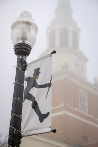 A light pole banner showing the profile of the Deacon wearing a mask. Behind the banner, Wait Chapel is seen through the fog