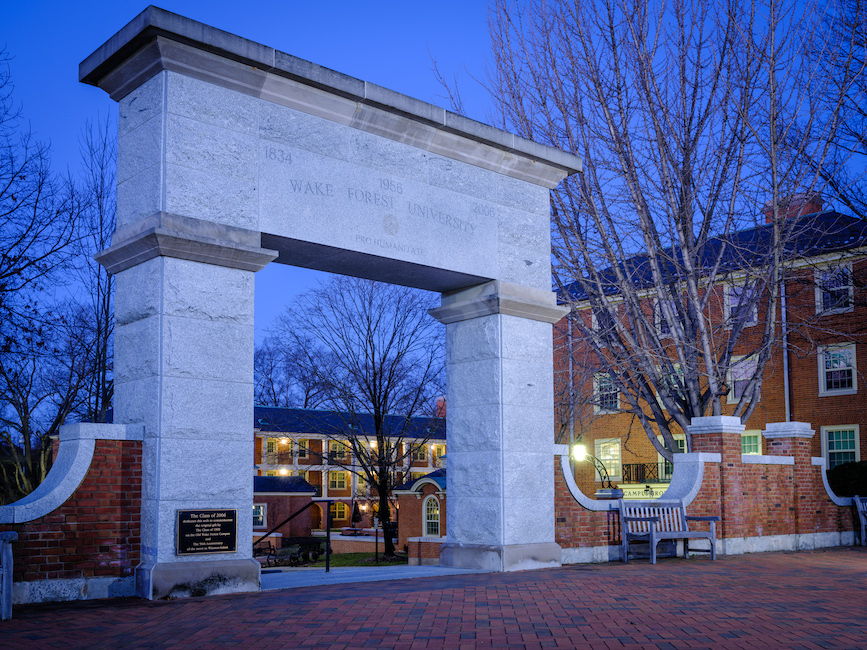 "Photo at dusk of the stone arch that marks the entrance to Hearn Plaza. ""Wake Forest University"" and the years 1834, 1956 and 2006 are carved in stone."