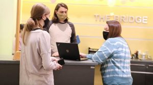 Photo of two students and a staff member wearing masks at the IS Service Desk