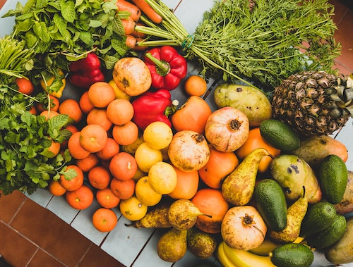 Photo of a pile of fruits, vegetables, and herbs (oranges, cucumbers, carrots, peppers, mint)