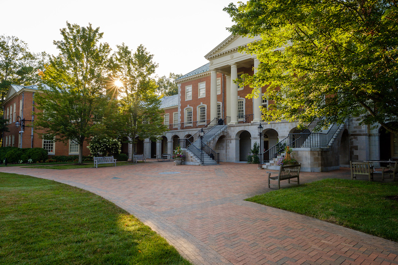 Photo of Reynolda Hall as seen from Hearn Plaza with the sun peeking through the trees