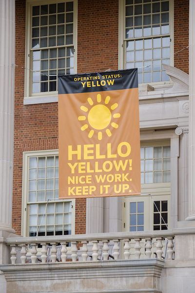"Photo of a banner hanging on the Z. Smith Reynolds library with the text ""Operating Status: Yellow"" above an image of the sun. Below the sun, text says ""Hello Yellow! Nice work. Keep it up."""