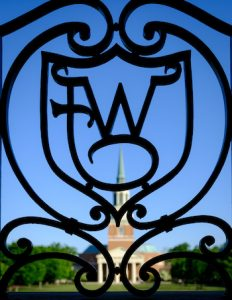 Wait Chapel is visible through an ironwork WF logo, on the campus of Wake Forest University