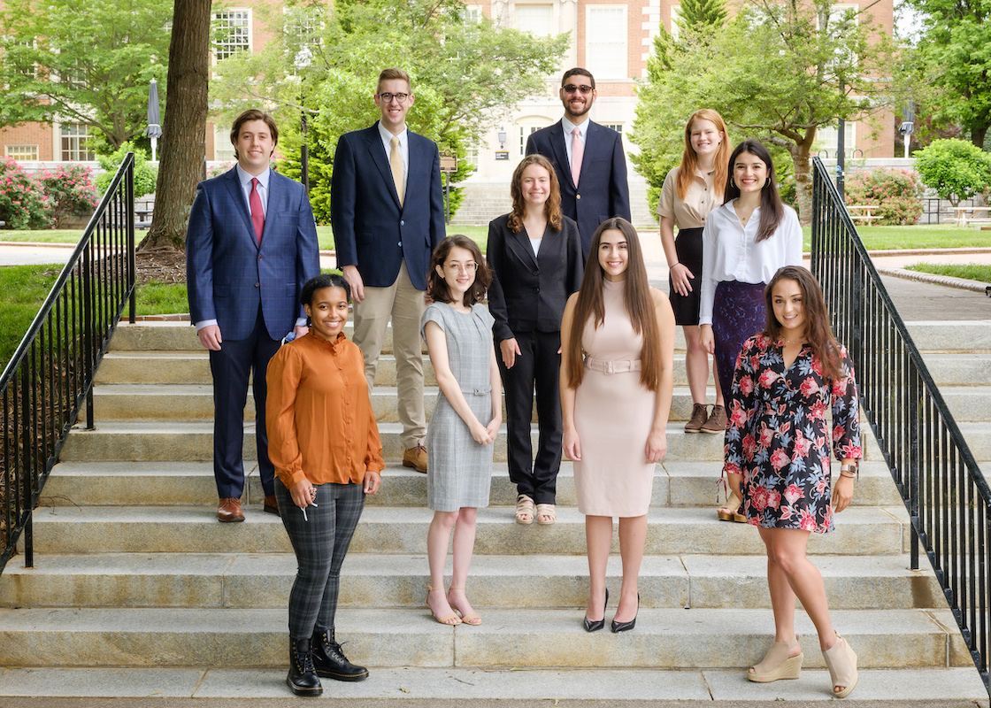 The Wake Forest Fellows for the 2021-22 academic year pose for a group portrait on the stairs in front of the Tribble Courtyard