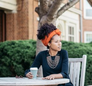 """Photo of Wake Forest faculty member Rowena """"Rowie"""" Kirby-Straker sitting at an outdoor table with a cup of coffee"""