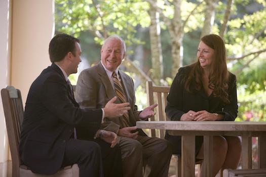 Photo of Professor Bern Beatty sitting at a table outside of Farrell Hall with Bern Beatty Scholars Lori Bremer (MBA '07) anad Karl Burns (MBA '08)