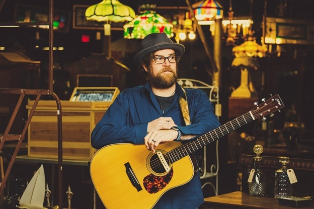 Photo of musician Aaron Burdett with his guitar standing an a cozy music hall