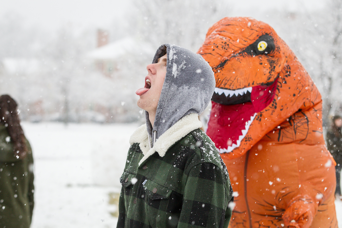 Student in dinosaur costume sneaks up on student on the Quad in the snow