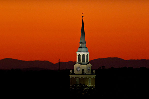 The bell tower of Wait Chapel rises in front of the sunset on the campus of Wake Forest University on Saturday, October 15, 2011.