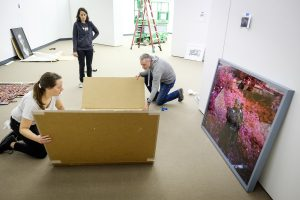 """New works in the Wake Forest Student Union Collection of Contemporary Art are unwrapped for a exhibit in the Hanes Art Gallery on campus on Monday, September 11, 2017. Paul Bright and Katie Wolf unwrap """"Man Size"""", a photograph by Richard Mosse."""