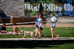 A Wake Forest student walks her dog with friends on Manchester Plaza as she enjoys a perfect early spring day.