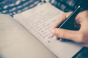 Photo of a man's hand checking items off of a to-do list