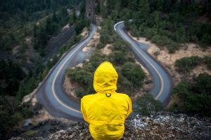 Person in yellow jacket overlooking roadway from mountain