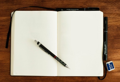 Open notebook with blank white paper and a pen