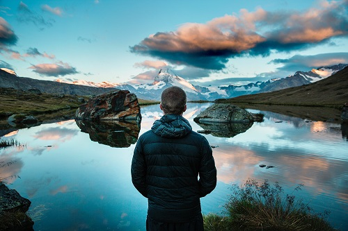 Man looking out over water and rocks at sunset