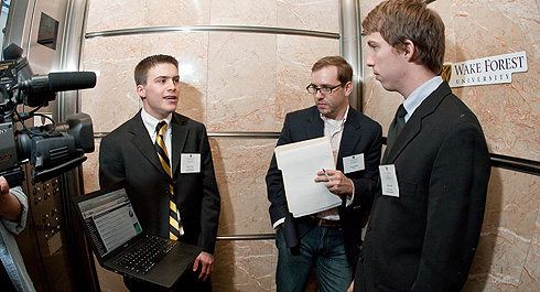 Sophomore Ben Comer (at left) and junior Brett Apter (at right) describe their new Web site, MySavu.com, to one of the judges in the Babcock School's annual Elevator Competition during a two-minute elevator ride at the Wachovia Center in downtown Winston-Salem on March 28.