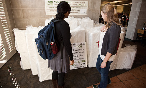 Students look at a pile of 7,000 Styrofoam boxes in the Fresh Food Company that will be replaced by reusable to-go boxes.