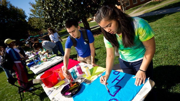 First-year student Keirah Carmichael (right) paints a shirt to hang on the clothesline.