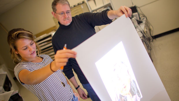 Assoc. Prof. John Pickel helps a student with her video art project.