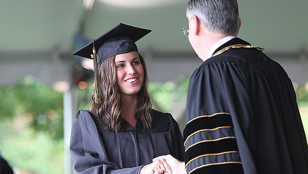 President Hatch shakes hands with a graduate.