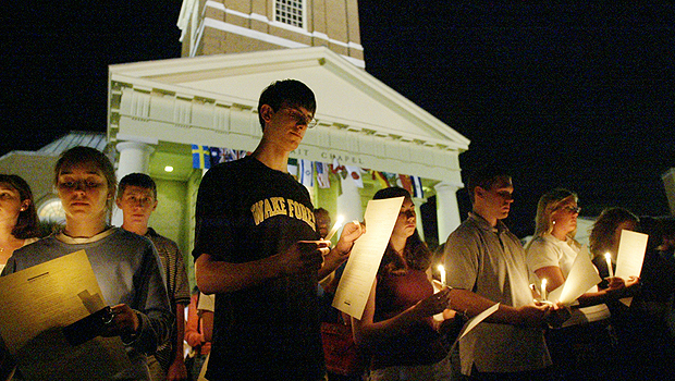 Student holding candles in front of Wait Chapel