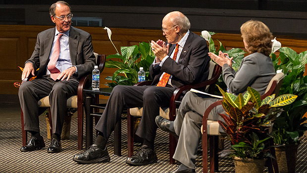 Alan Simpson and professor Katy Harriger applaud a point by Erskine Bowles (left).