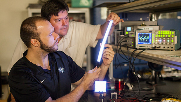 Professor David Carroll works with graduate student Greg Smith on the new lighting technology, FIPEL.