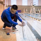 "Wake Forest sophomore Yinger ""Eagle"" Jin ('16) demonstrates his wave-powered electric generator in the pool in Reynolds Gym. The system harnesses the wave action as it compresses air inside the tube, which turns a small turbine that generates electricity."