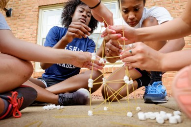 Lauren Brown, left, from Brooklyn, NY, and Dana Harvey, from Atlanta, work with their teammates to build structures out of marshmallows and spaghetti.